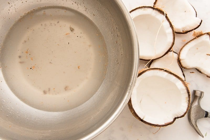 A silver mixing bowl with water from the cracked coconuts on the side of the bowl.