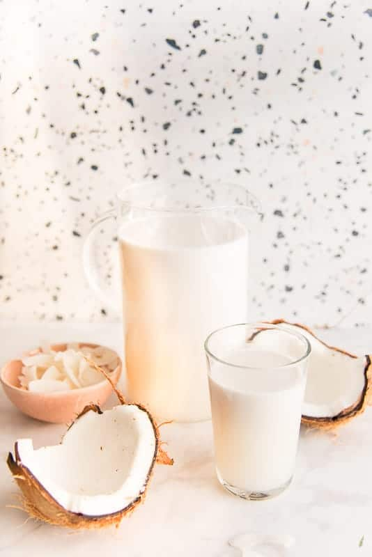 A glass of coconut milk next to a cracked coconut, behind: a glass pitcher of coconut milk next to the other coconut half