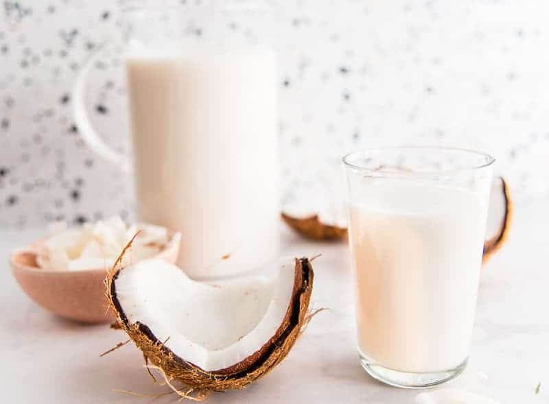 Close-up: glass of coconut milk next to a cracked coconut, behind: a glass pitcher of coconut milk next to the other coconut half