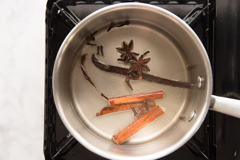 A tea is heated in a silver pot with the spices used to flavor the drink