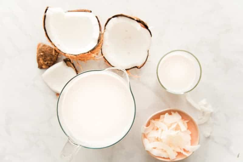 The finished coconut milk in a glass pitcher next to a glass of coconut milk. A pink bowl of dried coconut shavings is next to the pitcher and a cracked coconut is next to the glass of milk