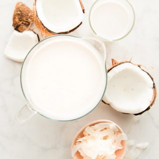 Overhead image of a pitcher of Coconut Milk, a coconut cracked open, a pink bowl with coconut silvers and a glass of coconut milk