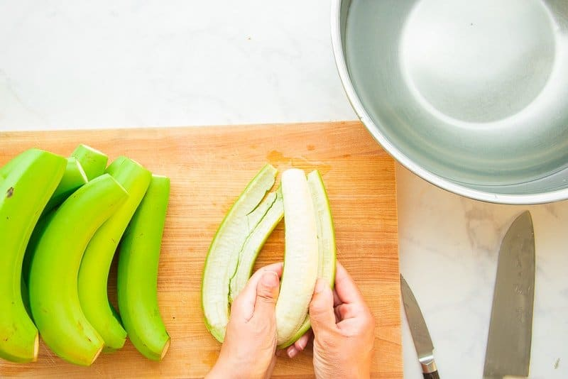 Green cooking bananas are peeled by two hands next to a silver bowl filled with saltwater