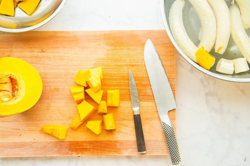 Orange calabaza (kabocha squash) is cut in chunks on a wooden board
