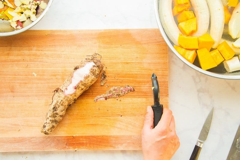 A piece of brown malanga (or yautía) is peeled with a vegetable peeler on a wooden cutting board to reveal the white flesh.