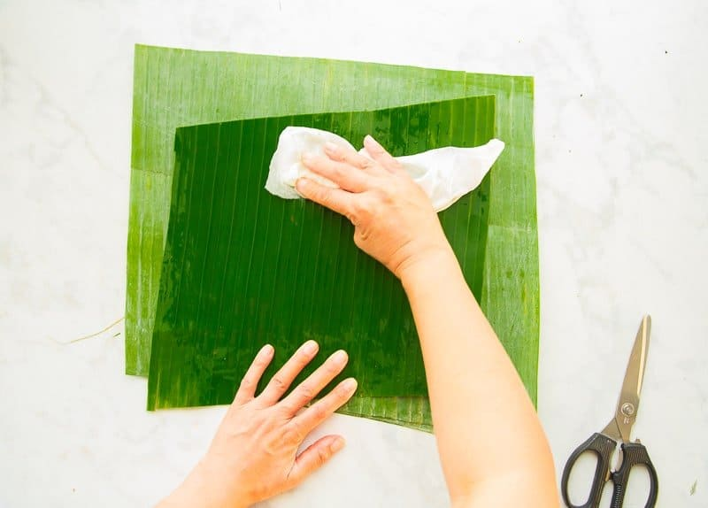 The green banana leaves are wiped down with a white rag to clean them.