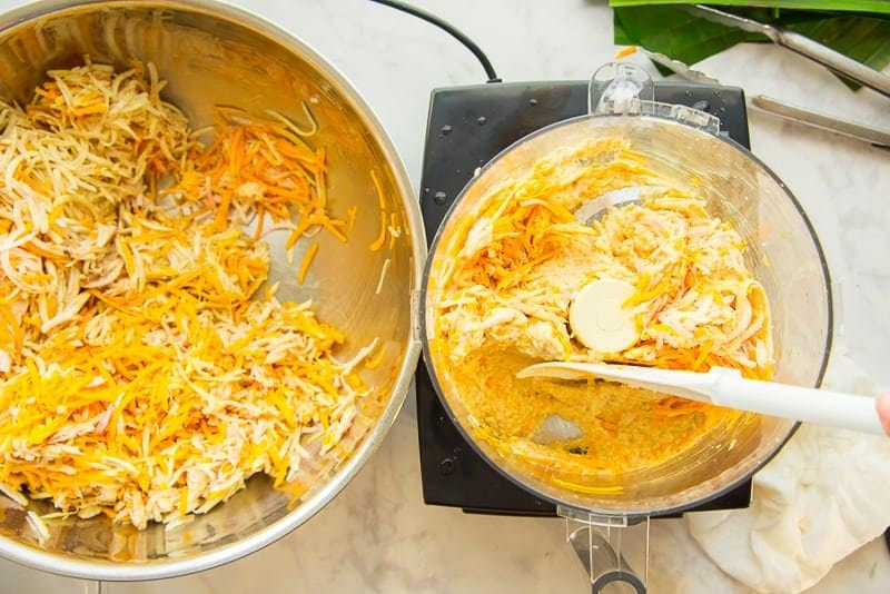 The shredded root vegetables are pureed in a food processor next to a silver bowl filled with the vegetables