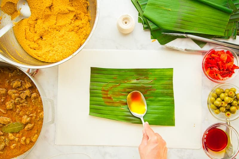 A large spoon spread achiote oil over the green banana leaf
