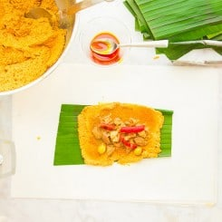 orange masa is on a green banana leaf and covered in pork filling, red pimentos, and two green olives