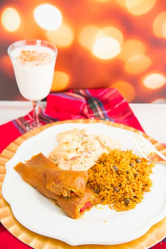 A long image of a white plate with pasteles, Puerto Rican rice, potato salad, and a glass of coquito in the background