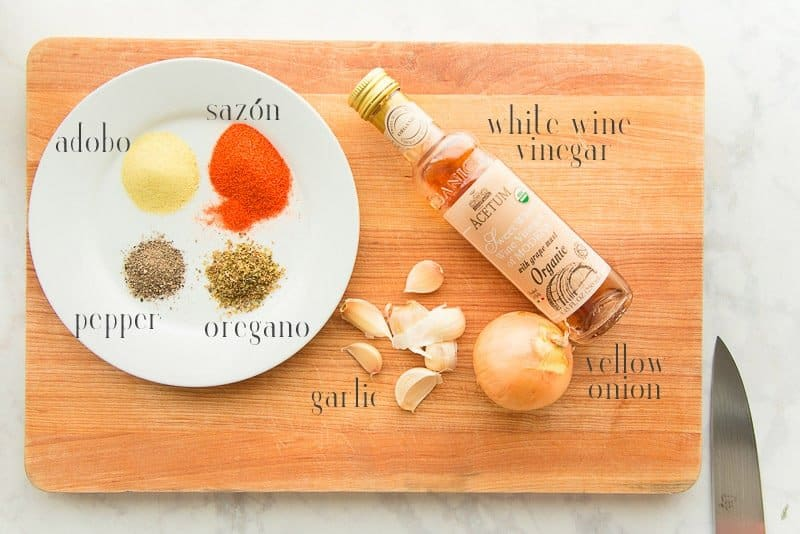 The spices for marinating pasteles meat on a white plate next to a bottle of white wine vinegar, a yellow onion, and 7 cloves of garlic all on a wooden board