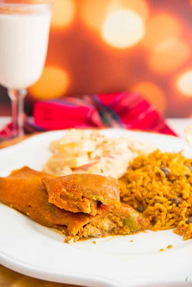 A portrait of a pasteles open to reveal the pork filling on a white plate along with arroz con gandules and potato salad.