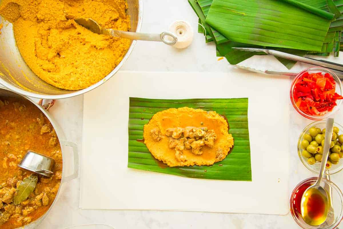 Preview of a green banana leaf with a mound of masa and the pork filling surrounded by pots of masa, pork filling, banana leaves, pimentos, olives, and oil