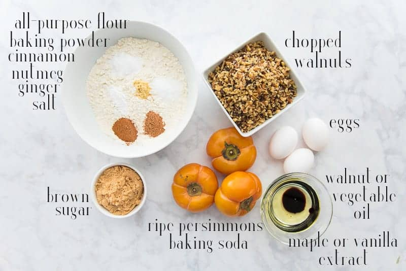 Ingredients to make persimmon-walnut muffins: flour and spices, walnuts, eggs, oil and extract, persimmons, and brown sugar