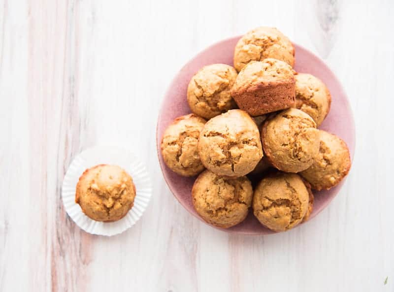 A pink plate piled high with persimmon-walnut muffins, a muffin sits on an open white muffin liner