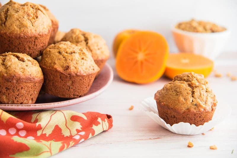 A single Persimmon-Walnut muffin on a white paper liner next to a pink plate of muffins.