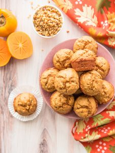 Long image pink plate with muffins. One muffin in a white wrapper on a wooden surface. A white bowl of chopped nuts.An orange persimmon cut in half leans against a whole fruit.