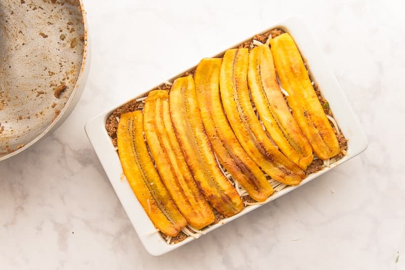 Fried plantain slices top the Vegan Pastelón in a white casserole dish