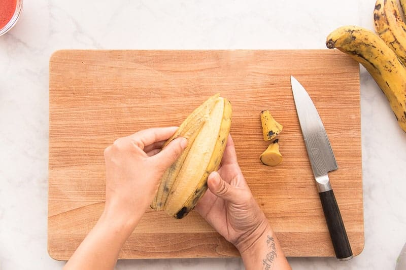 Two hands peeling a yellow plantain over a wooden cutting board