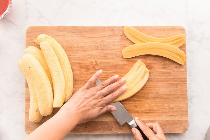 A hand holds a plantain in place while the other hand slices it into slabs with a knife