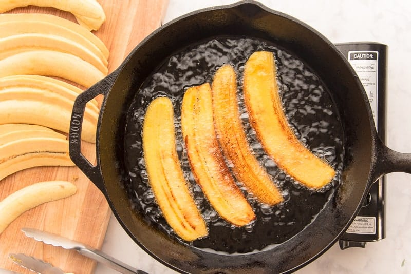 Four slices of yellow plantain are fried in oil in a black cast iron skillet