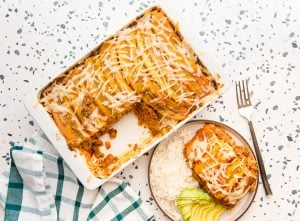 Horizontal image of a white casserole dish of baked vegan pastelón next to a plate with a serving of pastelón, rice, and avocado. Preview