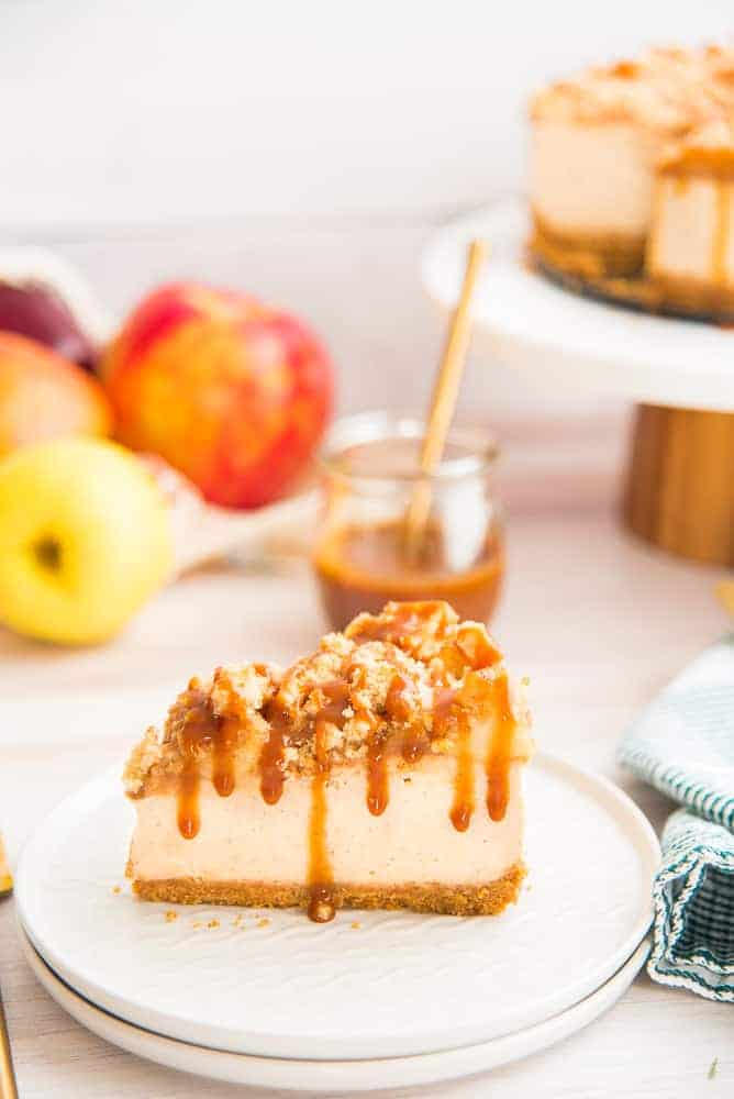 A portrait image of a slice of Apple Streusel Cheesecake on a white plate with apples in the background and a glass jar of caramel sauce.