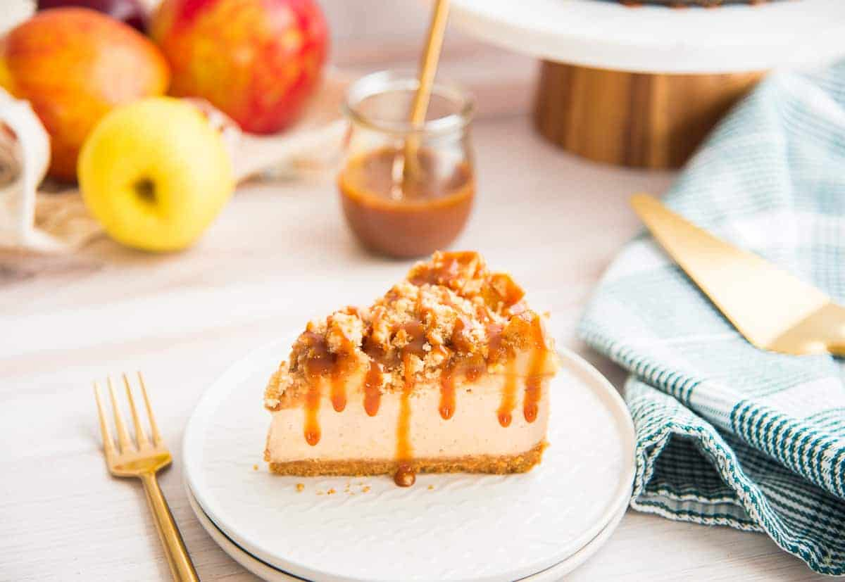 A horizontal image of a slice of Apple Streusel Cheesecake drizzled with caramel sauce on a white plate