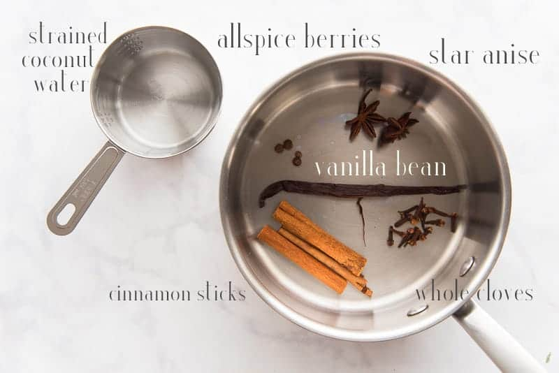 Ingredients to make the coconut spiced tea: filtered coconut water, vanilla bean, star anise, allspice, whole cloves, and cinnamon sticks in a silver pot.