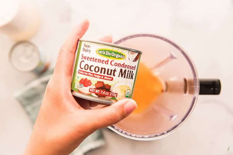 A can of sweetened condensed coconut milk is held over the blender before being added to it.