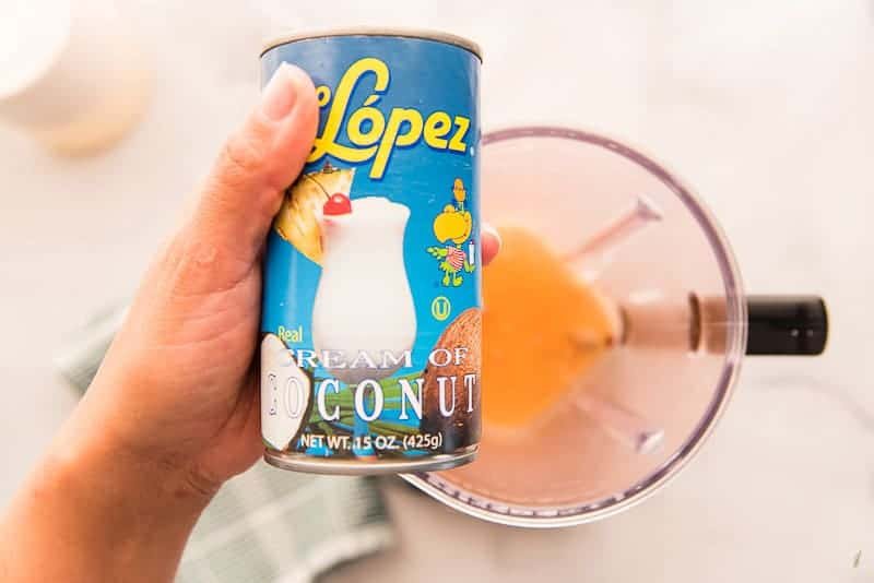 A blue labeled can of coco lopez cream of coconut is held over the blender.