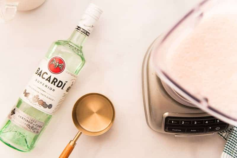 A bottle of Bacardi white rum is measured before being poured into the blender