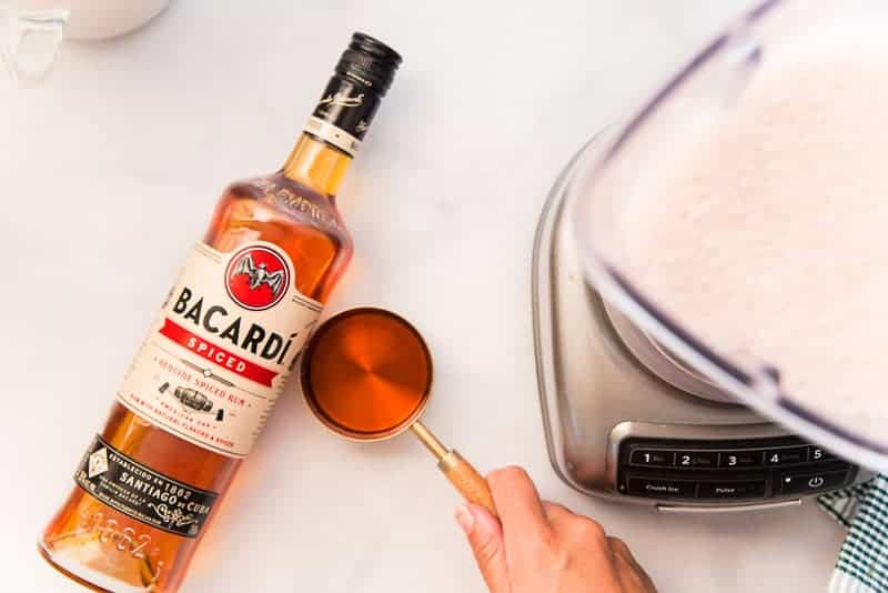 A bottle of bacardi spiced rum after being measured into a measuring cup and before being added to the blender