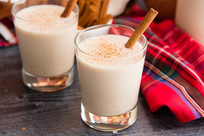 A glass of coquito garnished with a cinnamon stick next to a red plaid napkin