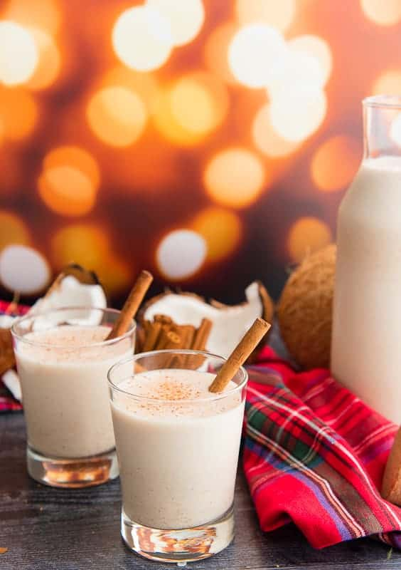 Two glasses of coquito garnished with cinnamon sticks in front of a twinkling background