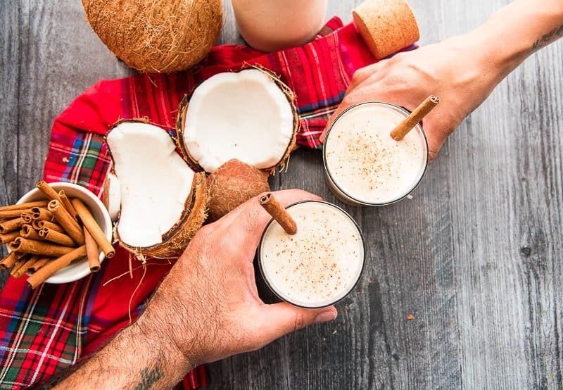 Two hands toast with glasses of coquito both glasses have cinnamon sticks in them