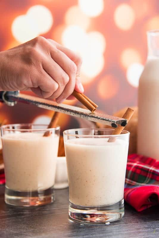 A hand grate cinnamon over a glass filled with coquito