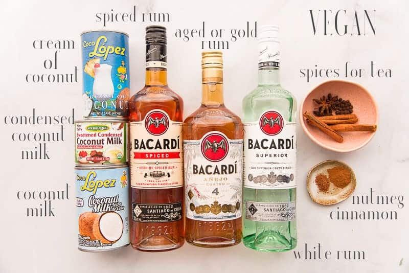 Ingredients for vegan coquito: cream of coconut, condensed coconut milk. coconut milk, spiced, añejo, and white rums, spices, nutmeg, and cinnamon