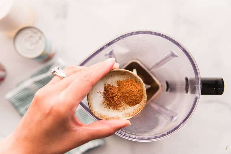 Ground cinnamon and nutmeg on a small brown plate held over a blender before being added to it.
