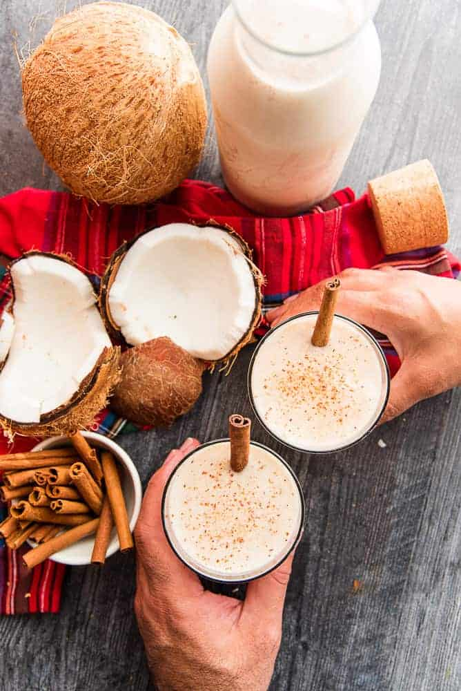 Two hands toast with two glasses filled with coconut rum cocktail