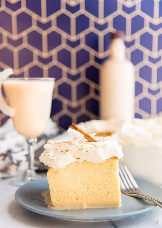 Coquito Tres Leches cake on a white plate in front of a blue art deco background