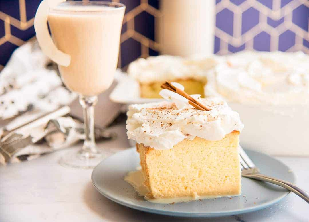 A yellow coquito tres leches cake topped with whipped cream on a grey plate