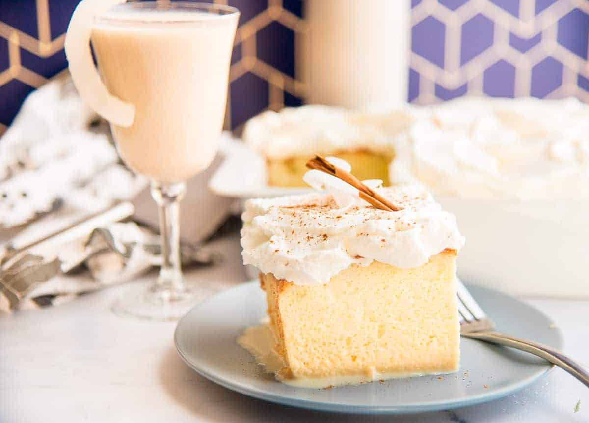 Yellow cake with white frosting on a grey plate. A glass of coquito is in the background.