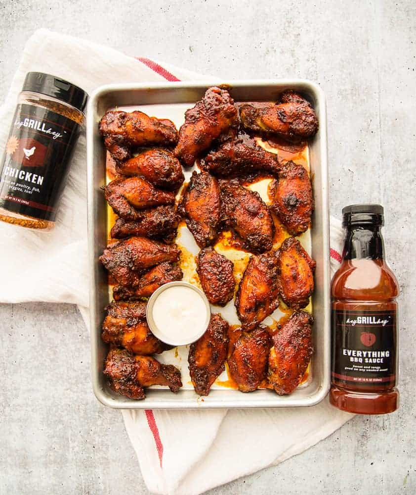 Lead image of a sheet pan with Guava BBQ Air Fryer Chicken Wings on a cement surface. Two bottle of Hey Grill Hey products surround the pan