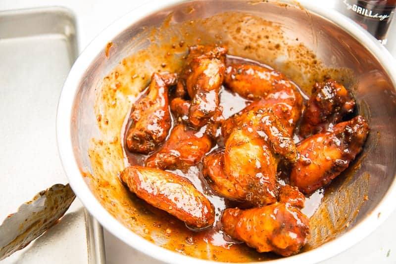 The air fried wings are tossed in the Guava BBQ sauce in a silver bowl