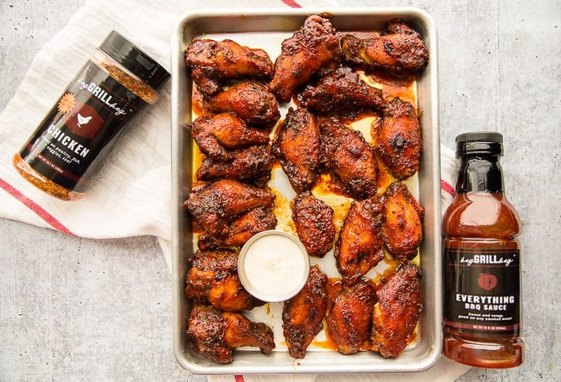 A silver sheetpan with Guava BBQ Air Fryer Wings on a cement surface. A bottle of spice rub and a bottle of BBQ sauce lie to the left and right