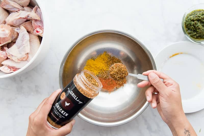 Spice rub is added to the other spices in a silver mixing bowl