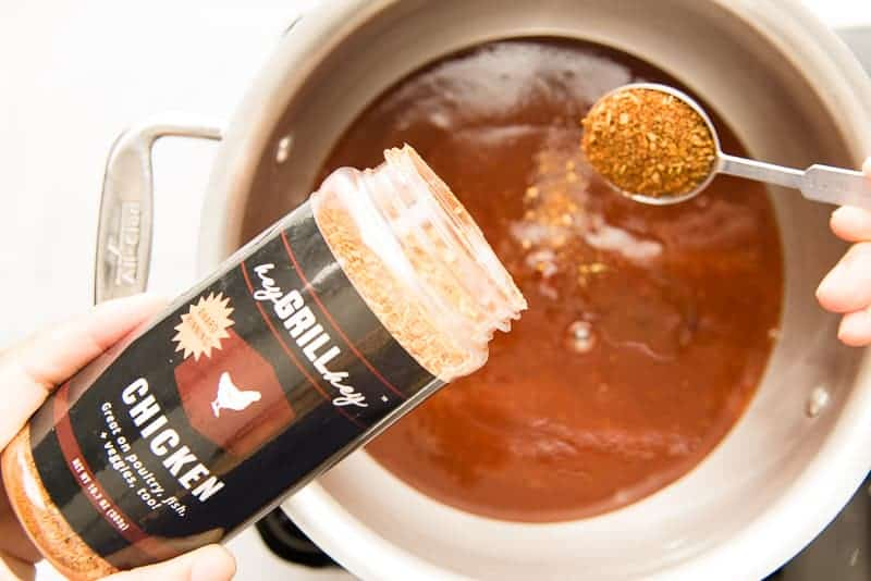 Spice rub is added to the sauce mixture in a silver pot