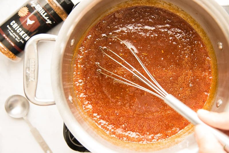 A whisk is used to stir the sauce in a silver pot