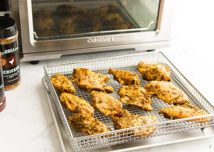 Marinated wings on a silver rack sit on a tray in front of the air fryer